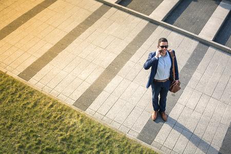 sidewalk talk: Businessman is speaking on the phone