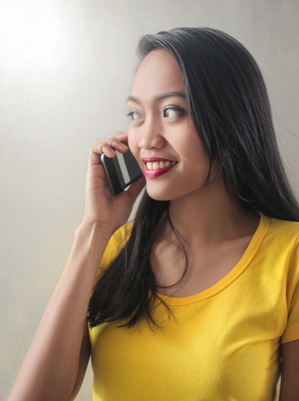 Pretty Asian girl is speaking on the phone Imagens