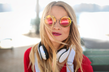 Young blonde girl with headphones in the wind Imagens