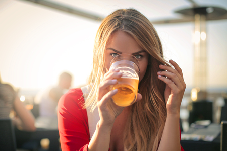 bebes lindos: Nice woman is drinking beer at a bar