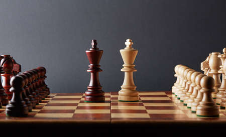 Classic Wooden Tournament chess set on black background. Two kings in centre of board other pieces lined up