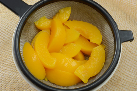 Rinsed canned peach slices in strainer draining water int white bowl