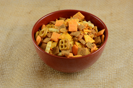 Red Bowl full of cheese flavored party snacks on burlap Banco de Imagens
