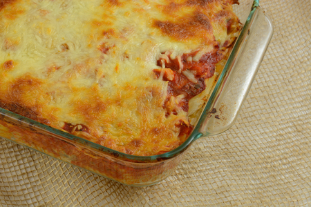 Close up of Baked casserole with melted cheese, marinara sauce, chicken and mixed vegetables on rotini pasta in glass baking dish Archivio Fotografico