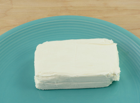 Block of cream cheese on blue plate