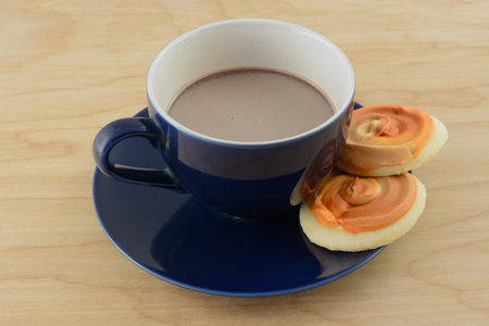 Cup of hot chocolate with two pumpkin frosted cookies on saucer