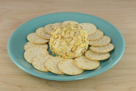 amaretto: White chocolate amaretto cheeseball with almond topping with table water crackers on blue plate