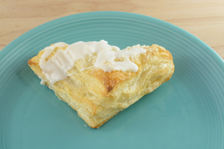 Apple turnover with frosting on blue plate Stock Photo