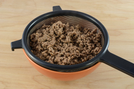 grease: Draining fat and grease from cooked hamburger meat in strainer in bowl for spaghetti sauce Stock Photo