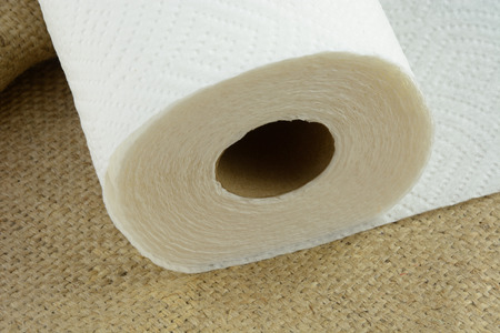 Close up of roll of paper towels on burlap
