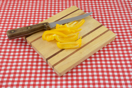 Yellow bell pepper slices on cutting board with knife