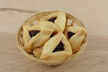 hamantash: Hamantaschen raspberry pastries in wicker basket on table