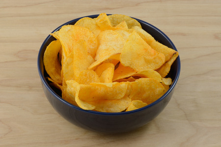 cheddar cheese: Cheddar cheese and sour cream flavored potato chips in blue bowl on table Stock Photo