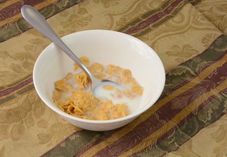 Corn flake cereal in milk in white bowl