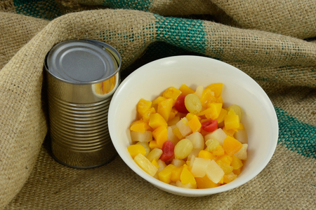 Canned fruit cocktail in bowl with can Archivio Fotografico