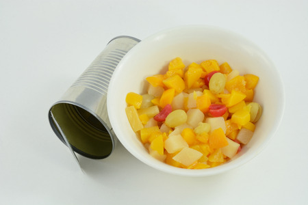 Canned fruit cocktail in bowl with can Фото со стока