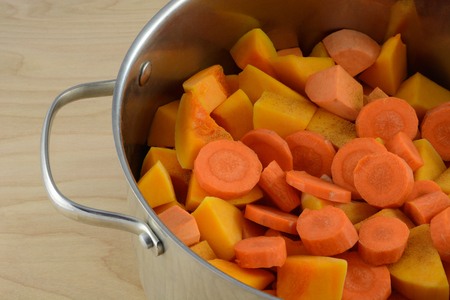Soup preparation with chopped carrots, butternut squash, yams. and spices in large soup pot Stock Photo