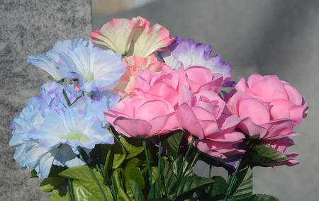 Artificial flowers left as memorial on gravestone Stock Photo