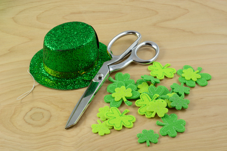 St. Patricks Day crafting project with green hat and shamrocks and scissors on table