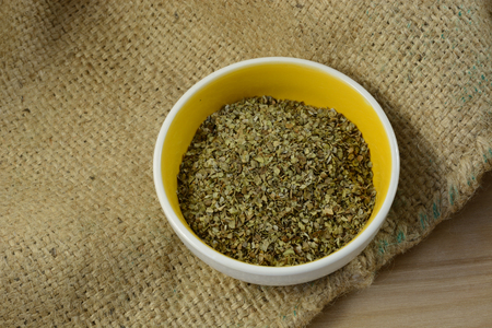 Marjoram leaves herb in small spice dish on burlap