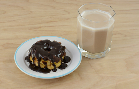 Triple chocolate breakfast with chocolate kefir and chocolate frosted donut smothered by chocolate syrup Stock Photo