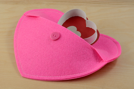 Heart emerging from pocket of larger pink heart Stock Photo