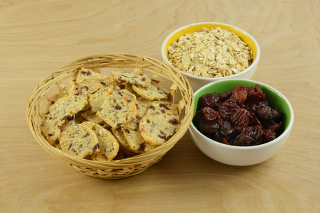 Cranberry oat crispbread snacks in wooden basket with bowls of dried cranberries and oats