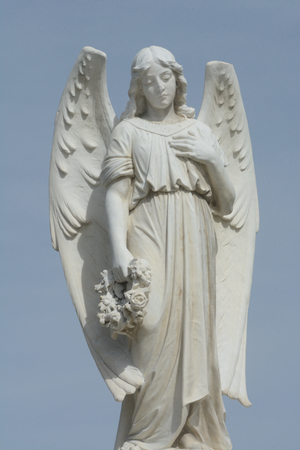 Gravestone memorial with angel holding wreath of flowers against overcast sky Stock Photo