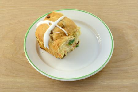 One hot cross bun on small bread plate