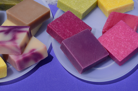 Colorful handmade beeswax soap squares on plates Reklamní fotografie