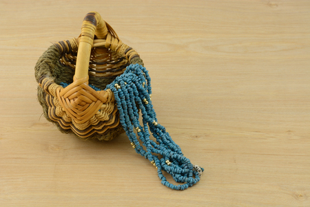 Blue necklace for work draped over handwoven wooden basket at end of day when changing from work clothes to informal recreational or at home clothes