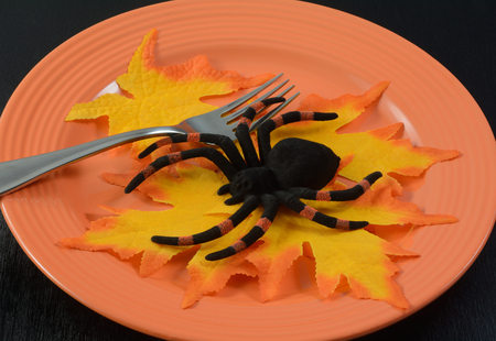 Halloween spider salad with autumn leaves on orange plate on black wood table