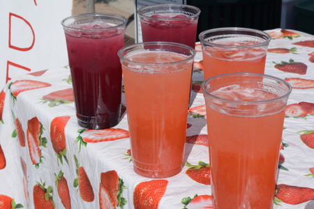 Glasses of blueberry and strawberry beverages with ice at lemonade stand at farmers market