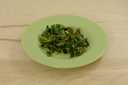 Cooked collard green salad on green plate Stock Photo