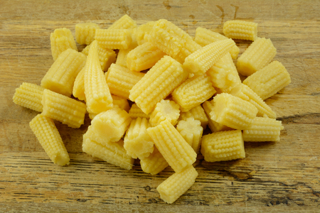 Close up of canned rinsed baby corn cobs on wooden cutting board