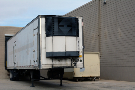 Shipping truck trailer parked at receiving door of business for unloading merchandise and or food Stock Photo