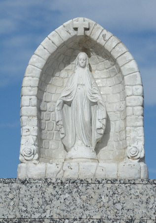 Small statuette of Blessed Virgin Mary in alcove as memorial on gravestone