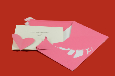 Opened Valentine card with note from mother and pink envelope and heart on red wooden table