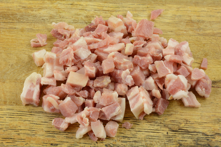 Preparing food with chopped raw pancetta bacon on rustic wooden cutting board Imagens