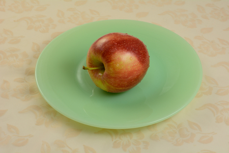One freshly rinsed Gala apple on green plate on tablecloth