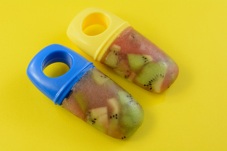 Two healthy homemade popsicles made from chopped kiwi fruit and cranberry juice on yellow background