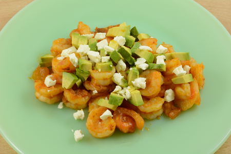 Spicy shrimp salad with chopped tomatoes, avocado, and feta cheese on green plate