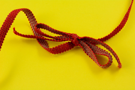 Red and gold ribbon and tied bow on yellow background Reklamní fotografie