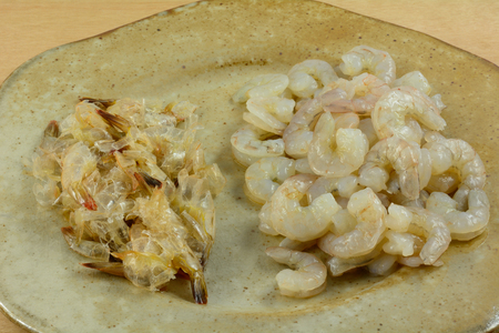platter with peeled raw headless shrimp on one side and empty skins on other Reklamní fotografie