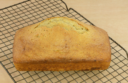 Whole loaf of homemade banana bread fresh out of oven on cooling rack