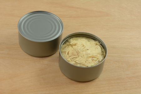 Two cans of albacore tuna fish with one can opened on wooden table