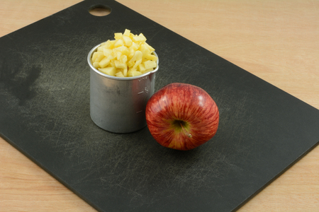 Whole raw Red Delicious apple and chopped apple in retro vintage metal measuring cup on cutting board
