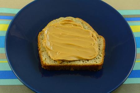 Healthy snack of peanut butter on slice of banana bread on blue plate Reklamní fotografie