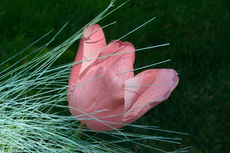 Pink artificial fabric tulip flower with thin green pine leaves