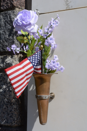 Patriotic grave memorial with all weather blue violet artificial flowers and American flag on mausoleum wall